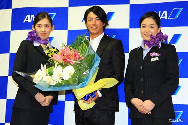 キャビンアテンダントから誕生日のお祝いに花束を受け取る石川遼