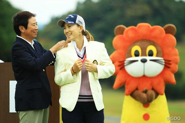 2014年 樋口久子 森永レディス 最終日 上田桃子 樋口久子大会名誉会長からチャンピオンブレザーの贈呈です。2人の表情も良くて、凄くイイ絵なのに、後ろのキャラクターが台無しにしてくれているような・・・。