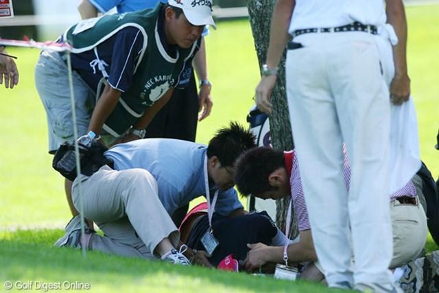12番ティ後ろで突然倒れた上田桃子(中央)を介抱するトレーナー。関係者らが心配そうに見守る