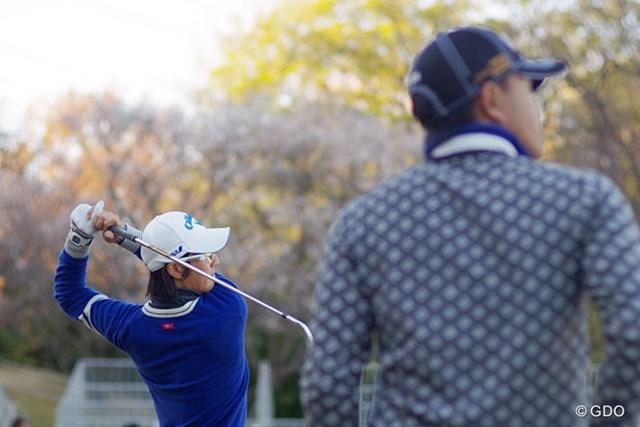 練習場で打ち込む石川遼と、それを見つめる小平智