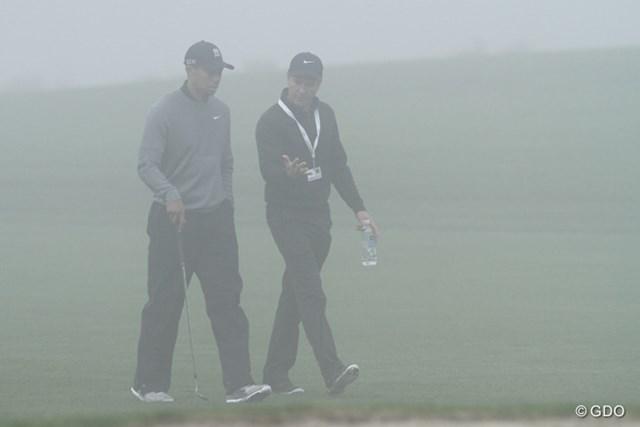 """深い霧が立ち込めたトーレパインズGCを""""スイング・コンサルタント""""のクリス・コモと歩くウッズ"""