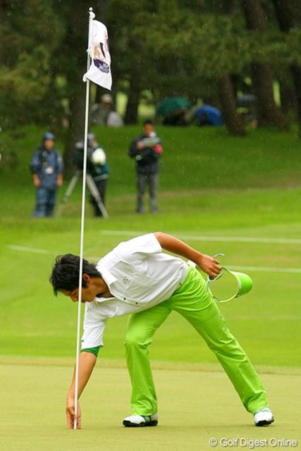 ギャラリーの大歓声を浴びながら、直接カップインしたボールを拾い上げる石川遼