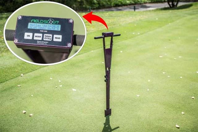 S吉クン12_水分計 これが水分計。芝に刺さっている先端部に2本の電極がある。体脂肪計のように、電極の間を流れる電気の抵抗を測って、水分の含有率を割り出す仕組み。