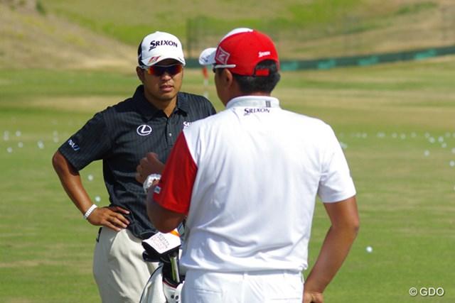 練習場で飯田光輝トレーナーと話す松山英樹。全英タイプのコースは好条件か