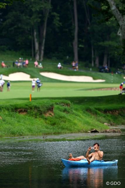 コース内を流れる川でくつろぐ男性と、コースでプレーする選手との緊張感の対比が大きすぎる