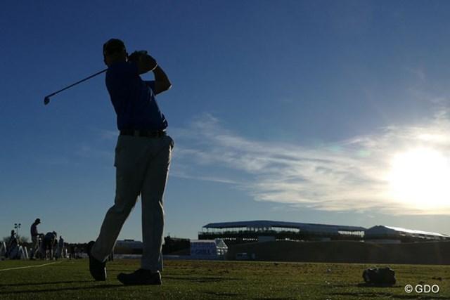 16番のスタジアムを背にドライビングレンジで練習する松山英樹