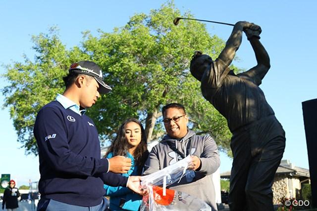 アーノルド・パーマーの銅像の前でギャラリーにサインをする松山英樹