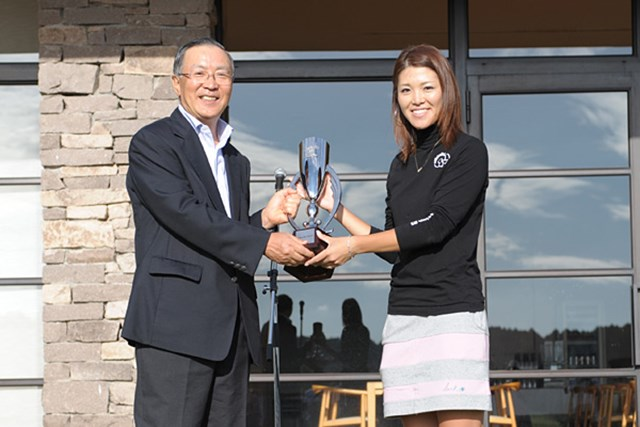 甲田良美 主催のライオン株式会社社長の藤重貞慶さんからカップを受けとる甲田良美