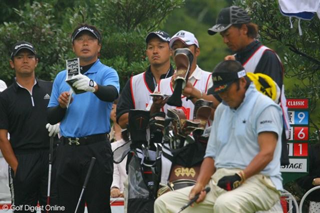 暫定首位タイとなった丸山大輔(左から2番目)。ティグラウンドではしきりに上空の雲をチェックしていた