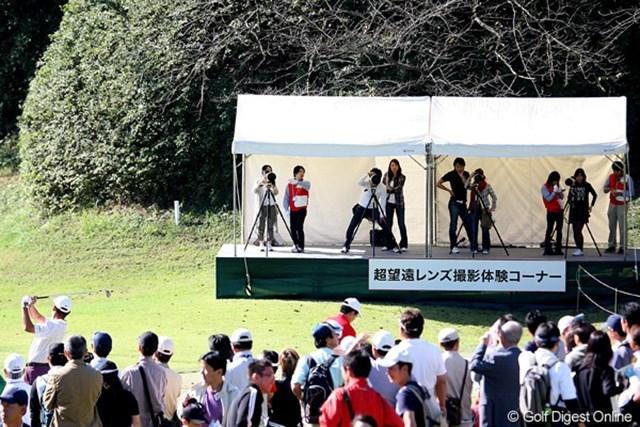 練習場の脇に、選手のスイングを正面から撮影できる「超望遠レンズ撮影体験コーナー」が設置。初めて手に大型レンズのカメラに興味深々。 使用カメラ:Canon EOS-1D Mark Ⅲ