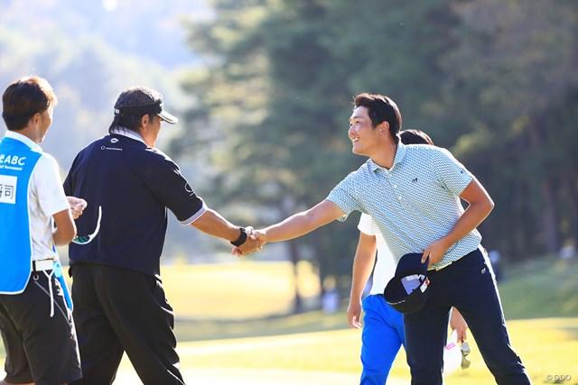 ラウンドを終えて笑顔で握手を交わす永野竜太郎と尾崎将司(左)