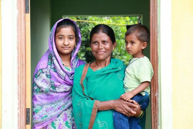 ハビタット・フォー・ヒューマニティらの支援によって建てられたオスマナバード(インド)の家の前に立つマンナビ(45歳)と義理の娘サナと孫のワジード。家は家族に安定とより良い未来への機会を与える。(Habitat for Humanity IndiaRitwik Sawant)