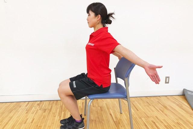 椅子に座った状態で腕を後ろに伸ばします
