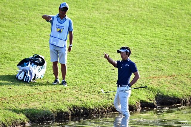 ボールは池の淵。左打ちを選ばず、水の中から方向を確認。