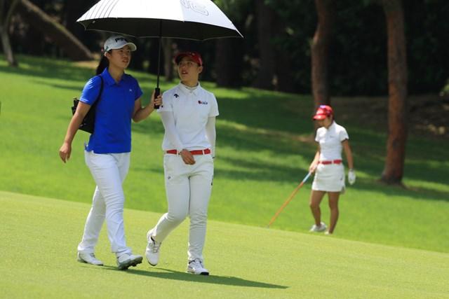 最終18番のフェアウェイを歩く吉田優利と上野菜々子。優勝争いをしていても日傘は一緒