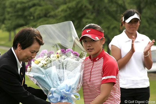 ローアマを獲得し樋口会長から花束を受け取る有村智恵。後ろはプレーオフで敗れた若林舞衣子