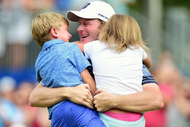 18番グリーン上で子供らと抱き合うスネデカー(Jared C. Tilton/Getty Images)