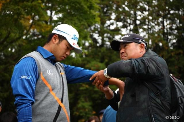 飯田光輝トレーナーに腕をほぐしてもらう松山英樹