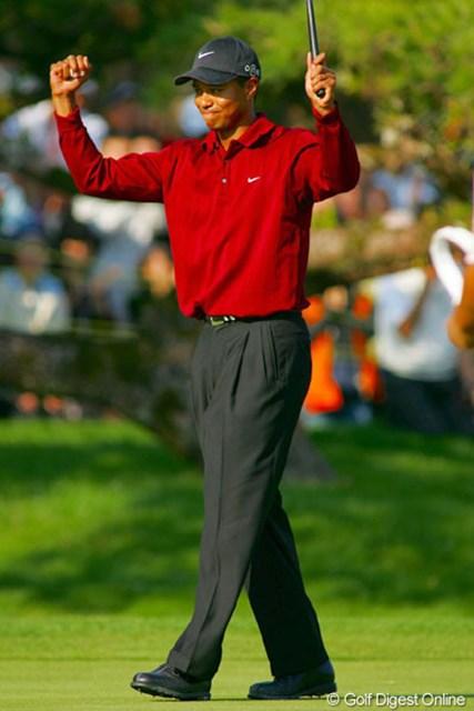 最終日18番、ウィニングパットを沈めて両手を挙げて喜びを表現するタイガー・ウッズ