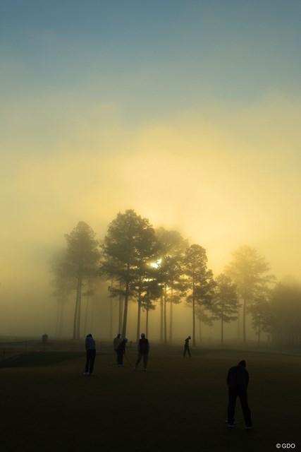 幻想的な朝もやの中、スタート前のパッティング練習をする選手達