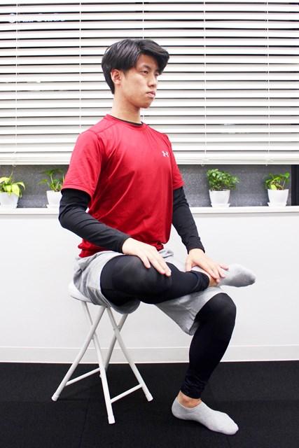椅子に浅く座り、片足を反対の膝に乗せます