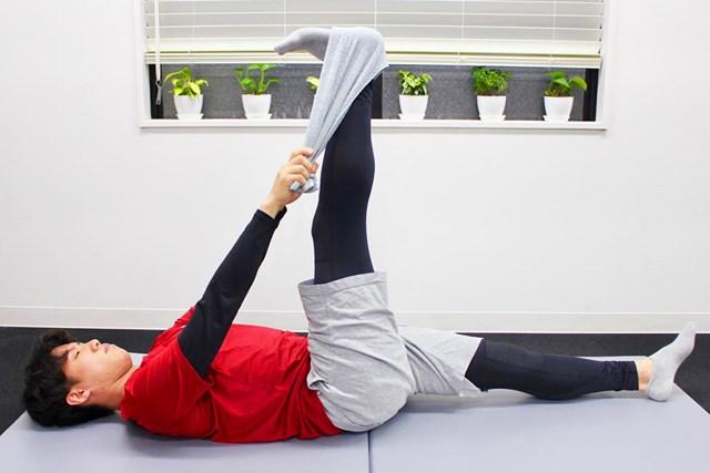 膝を伸ばし、タオルを両手で引っ張るように足を上げます