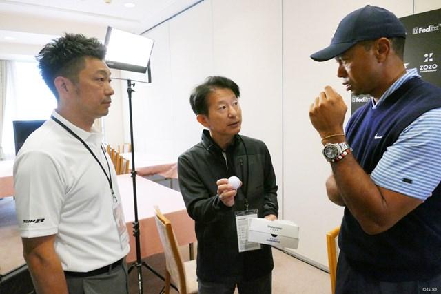 ウッズに新ボールを初披露するBSの甲斐氏(中央)と木村氏(左)