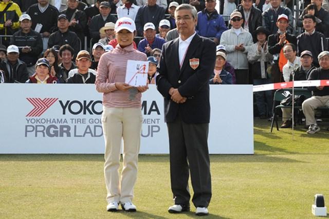 2010年 ヨコハマタイヤゴルフトーナメントPRGRレディスカップ最終日 永井奈都 ホールインワン賞の目録が南雲大会会長から永井奈都に手渡された