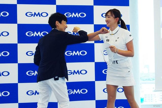 GMOインターネットグループ代表取締役兼社長の熊谷正寿氏と肘タッチする脇元華(右)
