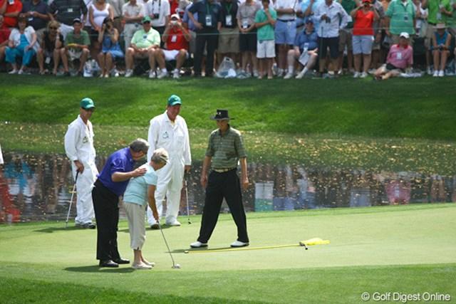2010年 マスターズ事前 ファジー・ゼラー 「これなら入るだろう」旗竿とウェッジでサポートし夫人にパットを打たせるファジー・ゼラー