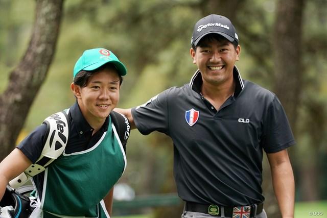 2020年 ダンロップフェニックストーナメント 2日目 石坂友宏 笑顔を見せる石坂友宏(右)。キャディは大学の後輩、鈴木遊大選手