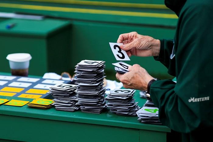 手動のリーダーボードのスコアの数字を整理するボランティア(提供:Augusta National Golf Club) 2021年 マスターズ 3日目 ボランティア