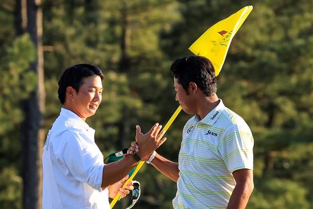 2021年 マスターズ 4日目 松山英樹 早藤将太 勝利の直後、お互いの「仕事」をたたえ合う松山英樹と早藤将太キャディ。左手にはマスターズの黄色いピンが握られている(提供:Augusta National Golf Club)