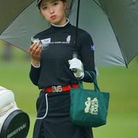 傘を差し、小脇にバッグを抱え、おにぎりを食べる。何とも言えずカワイイのです。 2021年 ワールドレディスチャンピオンシップサロンパスカップ 2日目 臼井麗華