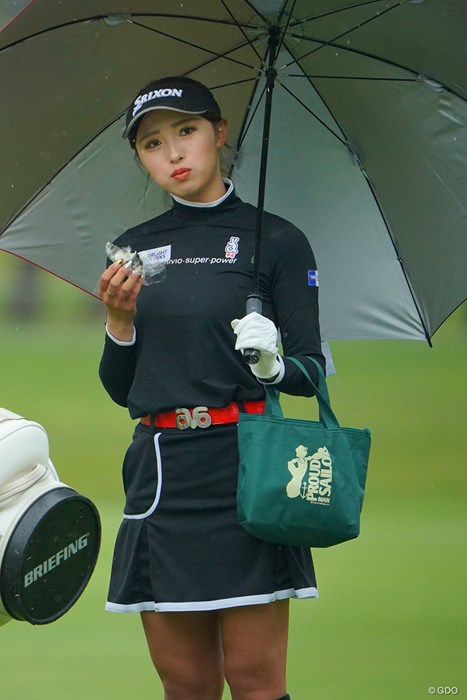 傘を差し、小脇にバッグを抱え、おにぎりを食べる。何とも言えずカワイイのです。 2021年 ワールドレディスチャンピオンシップサロンパスカップ 2日目 臼井麗香