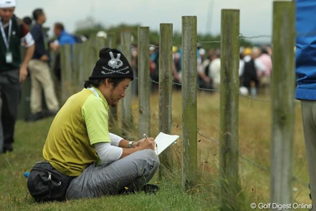 仕事マン今岡。柵の間から選手を覗いて、なにやらメモ。熱心に仕事中です