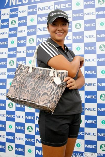 ホールインワンを達成した三塚優子に、主催のNECグループからイタリアブランド「フルラ」トートバッグが贈呈された