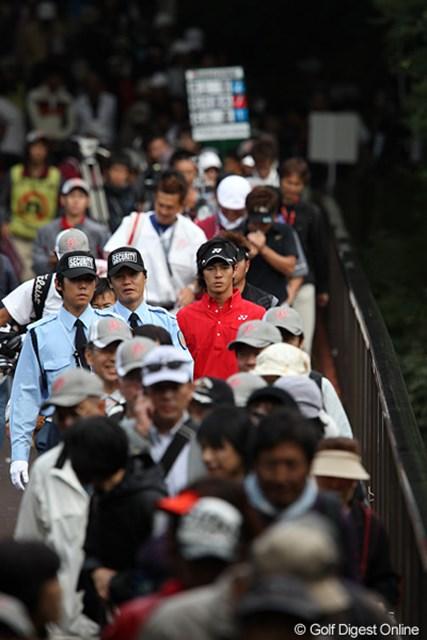 橋を渡る遼くんを2人の警備員がガードしてます。
