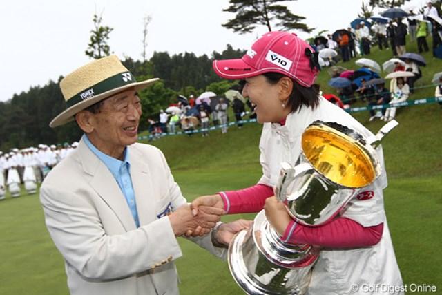 米山会長から優勝カップを手渡され笑顔で握手。