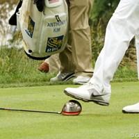 蹴っているわけではありません。ヘッドを踏んづけてグリップを上げ、拾っているだけなんです(でもダメ?) 2011年 全米オープン 最終日 アンソニー・キム