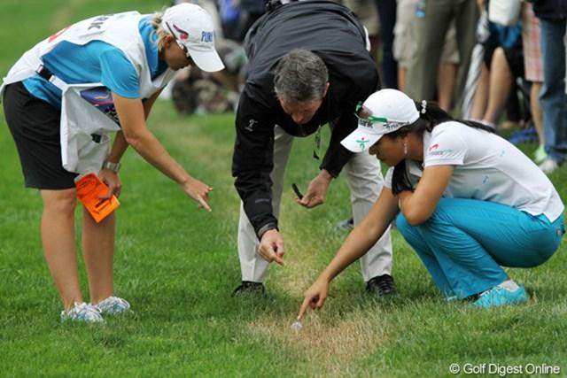 2011年 ウェグマンズLPGAチャンピオンシップ 最終日 救済措置 隠れた溝の上のボールが止まり、ルール委員とボールの下の地面を確認中