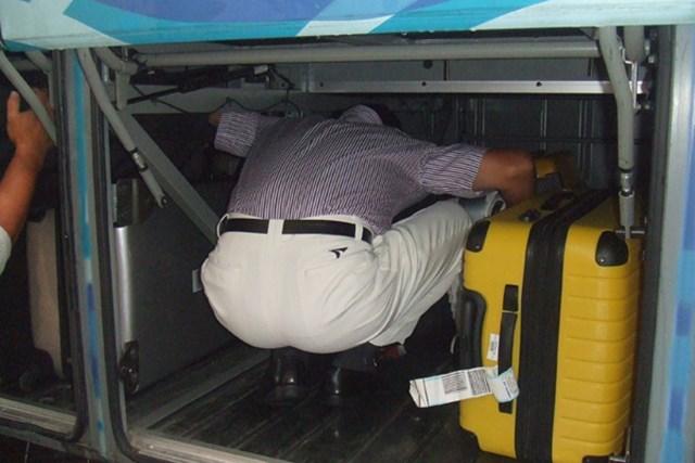 大型バスのトランクに頭を突っ込んで荷物を積み込んでいる選手・・・コレだ~れだ?