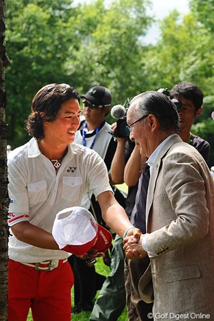 14番のグリーンサイドで観戦する長嶋茂雄大会名誉会長と握手を交わす石川遼