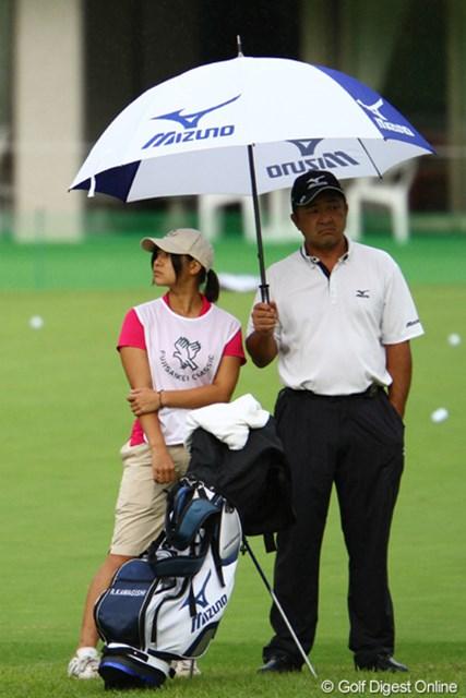 娘さんをキャディに起用した川岸さん。「イイじゃないかぁ。そんな嫌な顔しなくても。傘が一個しかないんだからぁ。」
