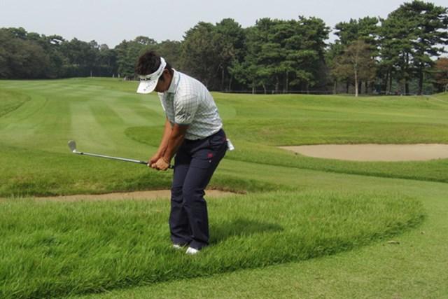 グリーン周りのラフから練習する藤田さん。両足が埋まります…(撮影・梅原敦)