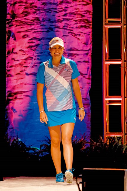 ショーでの緊張をはねのけ、笑顔で歩きだしたトンプソン。鮮やかな光に照らされながら、輝くステージに立った。(GW)