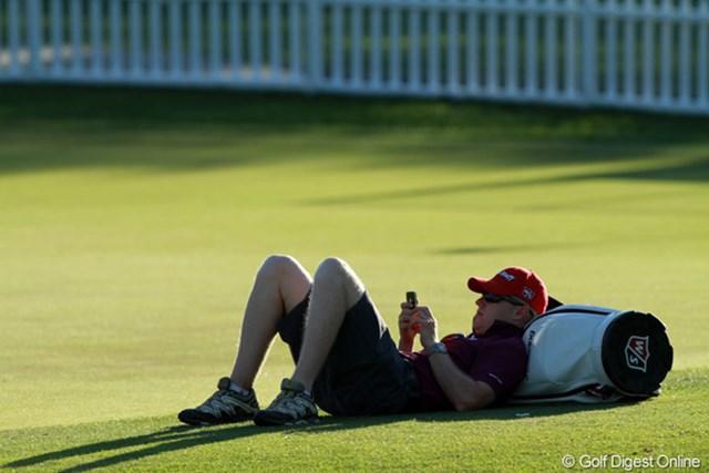 ハリントンのキャディはラウンド後に練習グリーンで一休み。「今日は一休みだよ」と余裕のコメント