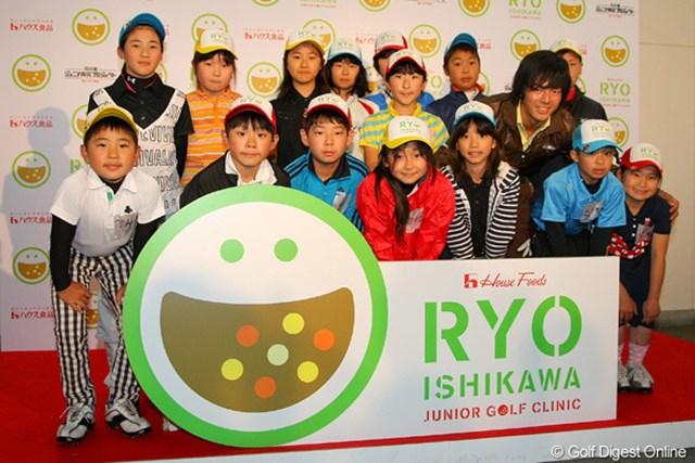 ジュニアゴルファーたちと笑顔で記念撮影に納まる石川遼。雨天の中、和やかなムードでイベントは進行した