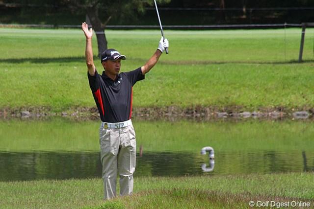 8番(パー3)でチップインバーディを決め、手を挙げて喜ぶ前回覇者の植田浩史