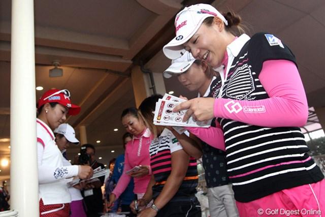 大会パンフにサインをする選手達、ちなみに表紙は昨年優勝の有村プロのイラスト